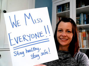 """Julie holding """"We Miss Everyone!!"""" Sign"""